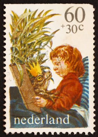 NETHERLANDS - CIRCA 1980: a stamp printed in the Netherlands shows Boy Reading King of Frogs, circa 1980 photo