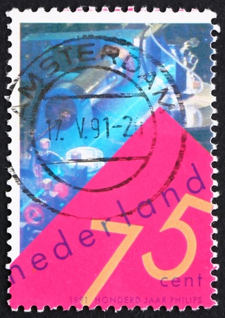 NETHERLANDS - CIRCA 1991: a stamp printed in the Netherlands shows Laser Video Disk Experiment, Centenary of Philips Electronics, circa 1991 photo
