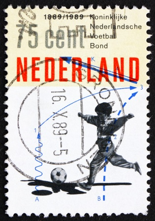 NETHERLANDS - CIRCA 1989: a stamp printed in the Netherlands shows Boy playing football, Centenary of Royal Dutch Soccer Association, circa 1989 Stock Photo - 12179783