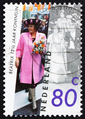 beatrix: NETHERLANDS - CIRCA 1992: a stamp printed in the Netherlands shows Queen Beatrix, 12 Years since Investiture, circa 1992 Editorial