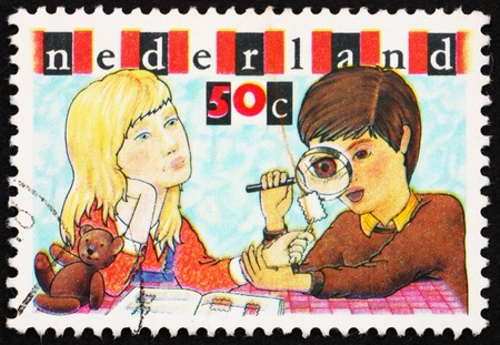 philately: NETHERLANDS - CIRCA 1980: a stamp printed in the Netherlands shows Boy and Girl Inspecting Stamp, Youth Philately, circa 1980