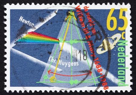 reloj de pendulo: PA�SES BAJOS - CIRCA 1988: un sello impreso en los Pa�ses Bajos muestra la luz del prisma Divisi�n, el planeta Saturno, reloj de p�ndulo, alrededor del a�o 1988