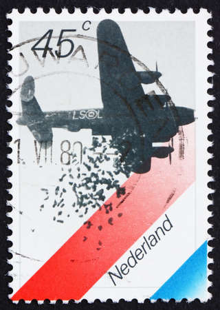 NETHERLANDS - CIRCA 1988: a stamp printed in the Netherlands shows British Bomber Dropping Food, Dutch Flag, 35th Anniversary of Liberation from Germans, circa 1988 photo