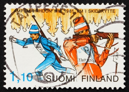 FINLAND - CIRCA 1980: a stamp printed in the Finland shows Biathlon, Winter Sport, cross-county skiing and rifle shooting, circa 1980 photo