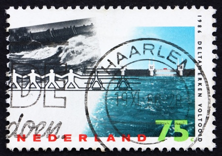 NETHERLANDS - CIRCA 1986: a stamp printed in the Netherlands shows Barrier Withstanding Flood, Delta Project Completion, circa 1986 photo