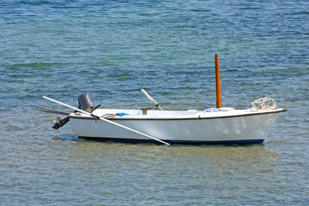 Lonely wooden fishing rowboat on the sea photo