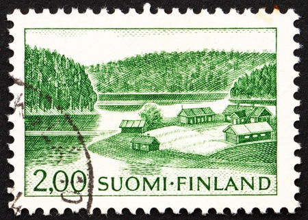 FINLAND - CIRCA 1964: a stamp printed in the Finland shows Farm on Lake Shore, circa 1964 photo