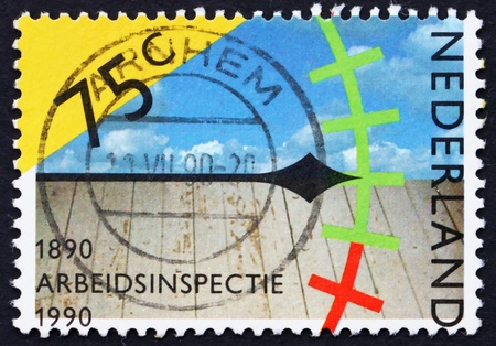 centenary: NETHERLANDS - CIRCA 1989: a stamp printed in the Netherlands shows Clock, Sky and Wooden Floor, Assessing Work Conditions, Centenary of Labor Inspectorate, circa 1989