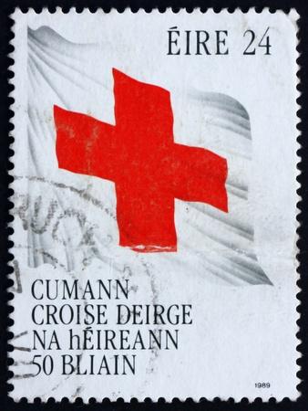 croix rouge: IRLANDE - CIRCA 1989: un timbre imprim� dans l'Irlande montre Drapeau Croix-Rouge, 50e anniversaire de la Soci�t� de la Croix-Rouge irlandaise, vers 1989 Editeur
