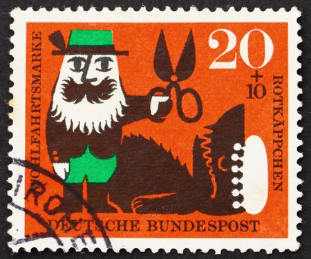 GERMANY - CIRCA 1960: a stamp printed in the Germany shows Forester and the Wolf, Scene from Little Red Riding Hood, circa 1960