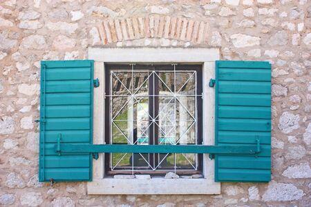 security shutters: Open green wooden window shutters, security element Stock Photo