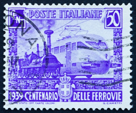 streamlined: ITALY - CIRCA 1939: a stamp printed in the Italy shows Wood-burning Engine and Streamlined Electric Engine, Centenary of Italian Railroads, circa 1939