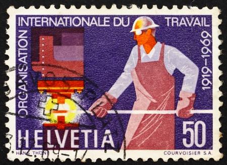 SWITZERLAND - CIRCA 1969: a stamp printed in the Switzerland shows Steelworker, 50th anniversary of the International Labor Organization, circa 1969 Stock Photo - 13685503