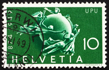 upu: SWITZERLAND - CIRCA 1949: a stamp printed in the Switzerland shows Figures Encircling Globe, 75th Anniversary of the UPU, circa 1949 Editorial