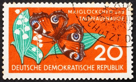 GDR - CIRCA 1959: a stamp printed in GDR shows Lily of the Valley and Butterfly, Nature, circa 1959 Stock Photo - 13860910