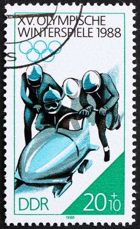 GDR - CIRCA 1988: a stamp printed in GDR shows 4-man Bobsled, 15th Winter Olympics, Calgary, Canada, circa 1988