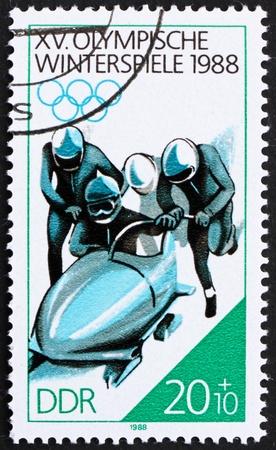 olympiad: GDR - CIRCA 1988: a stamp printed in GDR shows 4-man Bobsled, 15th Winter Olympics, Calgary, Canada, circa 1988 Editorial
