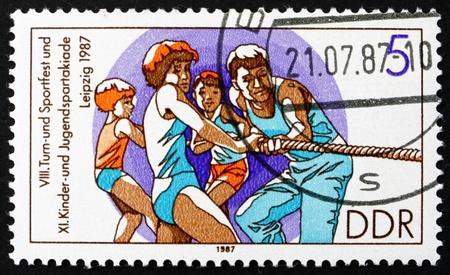 GDR - CIRCA 1987: un sello impreso en la RDA muestra tira y afloja, para niños y 11 jóvenes Spartakiade, alrededor del año 1987
