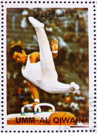 summer olympics: UMM AL-QUWAIN - CIRCA 1972: a stamp printed in the Umm al-Quwain shows Pommel Horse, Gymnastics, Summer Olympics, Munich 1972, circa 1972