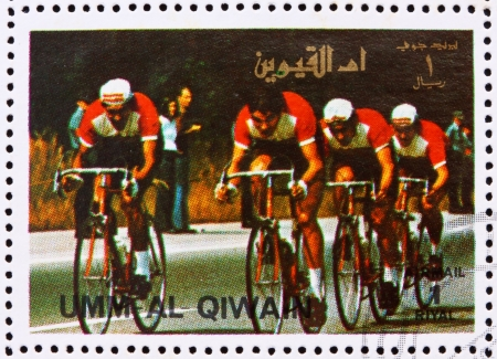perforated stamp: UMM AL-QUWAIN - CIRCA 1972: a stamp printed in the Umm al-Quwain shows Cycling, Summer Olympics, Munich 1972, circa 1972