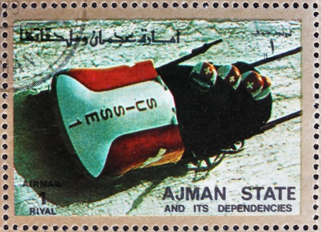 ajman: AJMAN - CIRCA 1973: a stamp printed in the Ajman shows Four-man Bobsled, Winter Olympics, circa 1973 Editorial