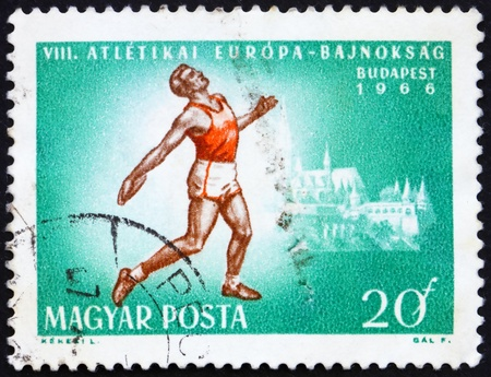 HUNGARY - CIRCA 1966: a stamp printed in the Hungary shows Discus Thrower and Matthias Cathedral, circa 1966 Stock Photo - 14224078