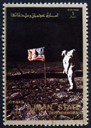 ajman: AJMAN - CIRCA 1973: a stamp printed in the Ajman shows Edwin Buzz Aldrin Salutes U.S. Flag on the Lunar Surface, Moon-landing, Apollo 11, circa 1973 Editorial