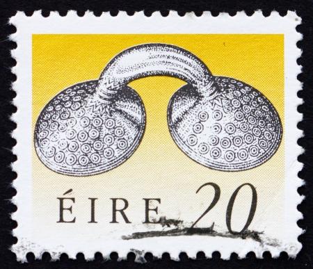 IRLANDA - CIRCA 1991: un sello impreso en la muestra de tornillos de oro de Irlanda vestido, el arte del Tesoro de Irlanda, alrededor del año 1991