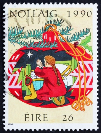 irish christmas: IRELAND - CIRCA 1990: a stamp printed in the Ireland shows Child Praying in a Christmas Decoration, Christmas, circa 1990