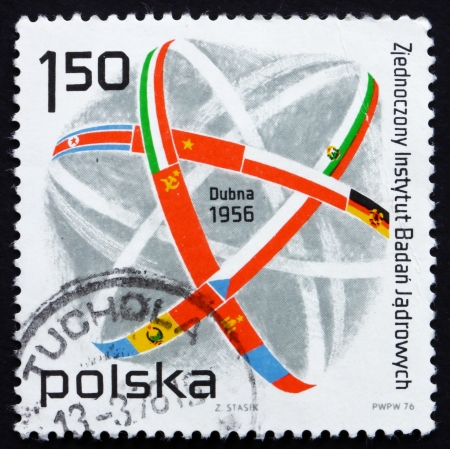 POLAND - CIRCA 1976: a stamp printed in the Poland shows Atom Symbol and Flags, 20th Anniversary of Joint Institute of Nuclear Research, Dubna, circa 1976 Stock Photo - 14406595
