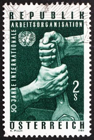 un used: AUSTRIA - CIRCA 1969: a stamp printed in the Austria shows Hands Holding Wrench, and UN Emblem, 50th Anniversary of ILO, circa 1969