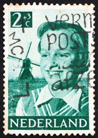 NETHERLANDS - CIRCA 1951: a stamp printed in the Netherlands shows Girl and Windmill, circa 1951