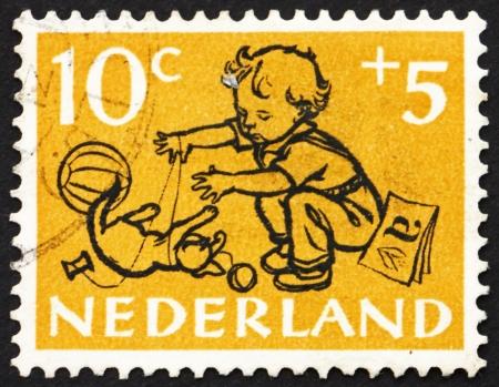 chłopięctwo: HOLANDIA - OKOŁO 1952: Stempel drukowane w Holandii pokazuje Boy and Kitten, circa 1952