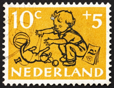 NETHERLANDS - CIRCA 1952: a stamp printed in the Netherlands shows Boy and Kitten, circa 1952
