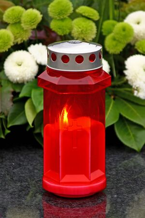Illuminated votive candle glows on a grawe lantern photo
