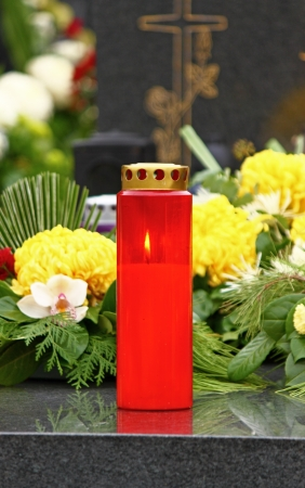 Illuminated votive candle glows on a grave, lantern photo