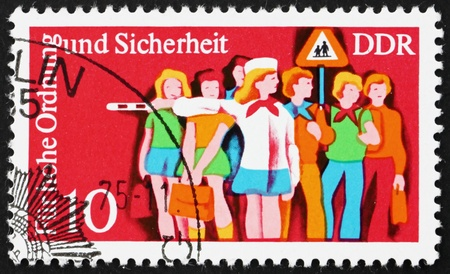 instructing: GDR - CIRCA 1975: a stamp printed in GDR shows Children and Child Crossing Guard, Traffic Police Serving and Instructing the Public, circa 1975 Editorial