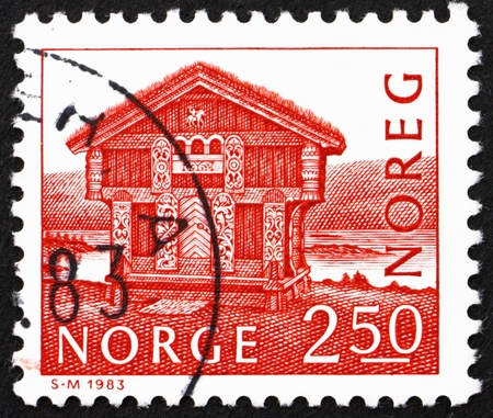 perforated stamp: NORWAY - CIRCA 1983: a stamp printed in the Norway shows Log House, Breiland, Norway, circa 1983 Editorial