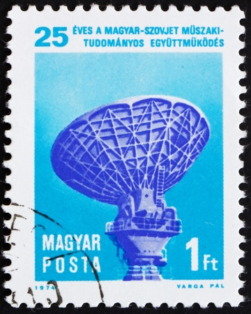 HUNGARY - CIRCA 1974: a stamp printed in the Hungary shows Intersputnik Tracking Station, 25th Anniversary of Technical Assistance between Hungary and USSR, circa 1974 Stock Photo - 15942861