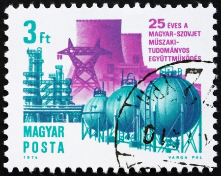 HUNGARY - CIRCA 1974: a stamp printed in the Hungary shows High Voltage Line and Pipe line, 25th Anniversary of Technical Assistance between Hungary and USSR, circa 1974 Stock Photo - 15942858