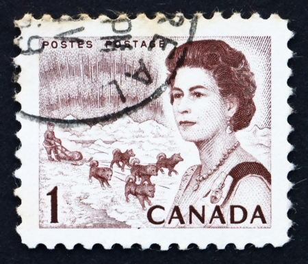 canada stamp: CANADA - CIRCA 1967: a stamp printed in the Canada shows Northern Lights and Dog Team, Queen Elizabeth II, circa 1967