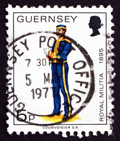 militia: GUERNSEY - CIRCA 1974: a stamp printed in the Guernsey shows Royal Militia, Uniform from 1895, circa 1974