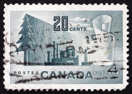 newsprint: CANADA - CIRCA 1952: a stamp printed in the Canada shows Symbols of Newsprint Paper Production, From Tree to Paper, circa 1952