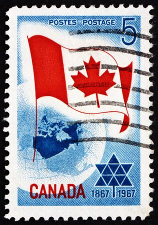 CANADA - CIRCA 1967: a stamp printed in the Canada shows Canadian Flag over Globe and Centennial Emblem, Canada�s Centenary as a Nation, circa 1967 Stock Photo - 16746188