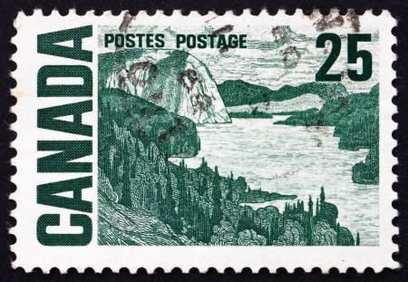solemn land: CANADA - CIRCA 1967: a stamp printed in the Canada shows The Solemn Land, Oil Painting by J. E. H. MacDonald, circa 1967 Editorial
