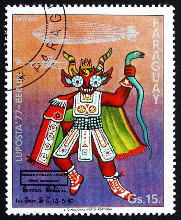 indian postal stamp: PARAGUAY - CIRCA 1977: a stamp printed in Paraguay shows Ceremonial Indian Costume, Bolivia, Graf Zeppelin 1st South America Flight, circa 1977 Editorial