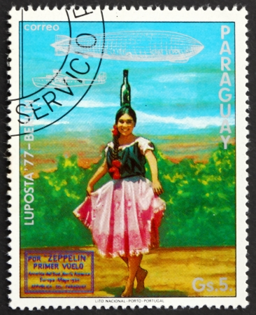 graf: PARAGUAY - CIRCA 1977: a stamp printed in Paraguay shows Indian Girl in Bottle Dance Costume, Graf Zeppelin 1st South America Flight, circa 1977 Editorial