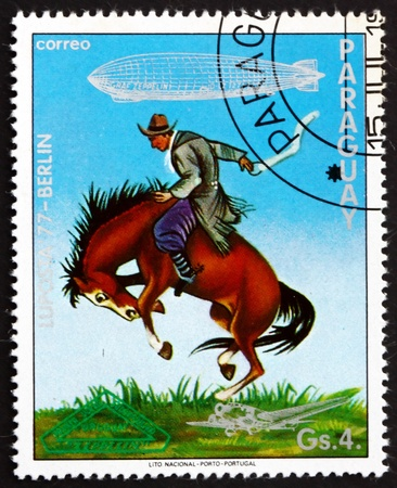 graf: PARAGUAY - CIRCA 1977: a stamp printed in Paraguay shows Gaucho Breaking Bronco, Uruguay, Graf Zeppelin 1st South America Flight, circa 1977 Editorial