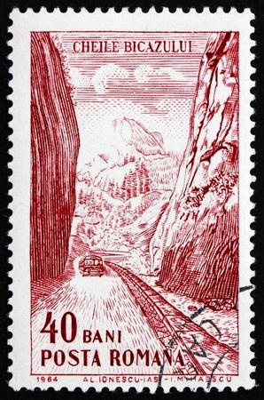 puertas de hierro: RUMANIA - CIRCA 1964: un sello impreso en Rumania muestra el camino a trav�s de Gorge, las Puertas de Hierro, Publicidad Tur�stica, alrededor de 1964 Editorial