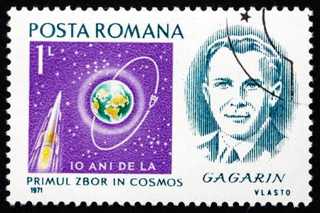 ROMANIA - CIRCA 1971: a stamp printed in the Romania shows Yuri Gagarin, 1st Man in Space, and Rocket Orbiting Earth, circa 1971 Stock Photo - 17063383